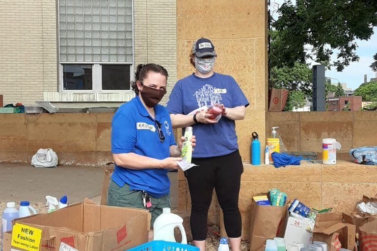 Liz (on the right) volunteering with NECHAMA at a food bank in June 2020.