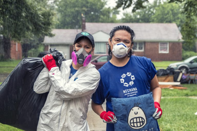 Michigan program extended. two volunteers pause for a photo in the rain, carrying items out of a flood damaged home in Detroit, Michigan.