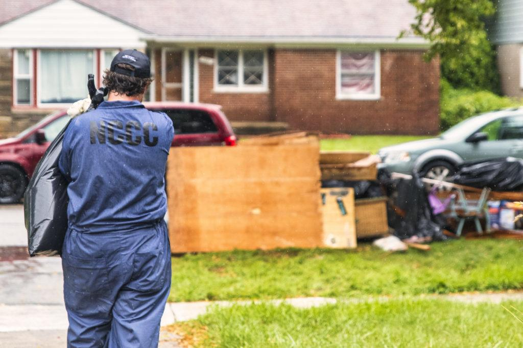 Team Maple 1 member carries a bag full of debris from a flooded home out to the pile on the curb