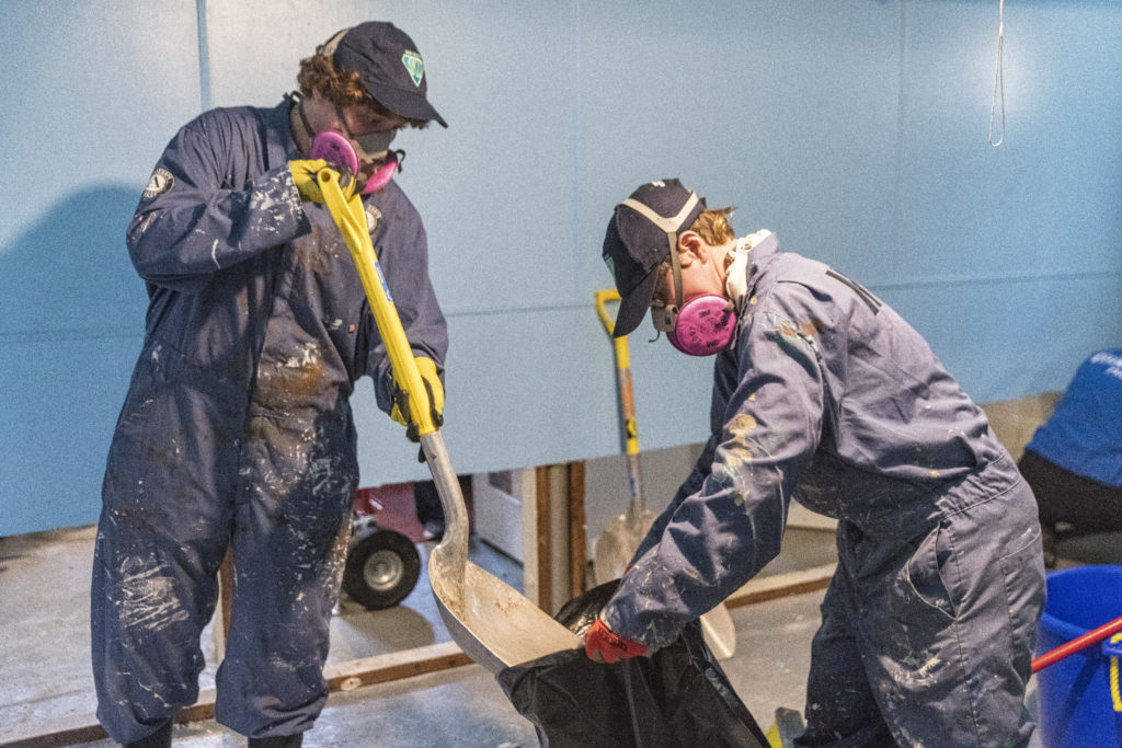 Team Maple 1 cleans debris from a flooded basement