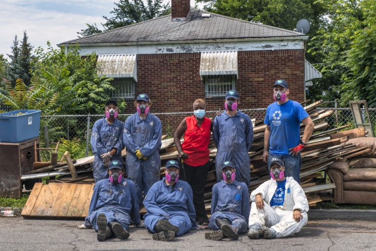 Team Maple 1 poses for a photo with a homeowner in front of the damaged items from their house piled behind them