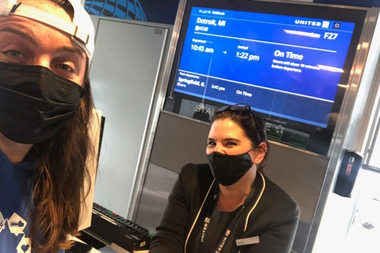 donate your frequent flyer miles! A Nechama volunteer is shown with a Delta airlines agent checking into a flight donated through Airlink